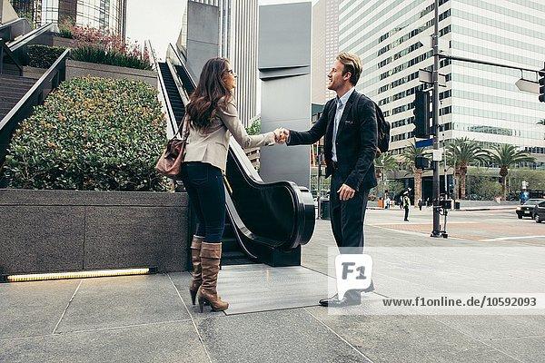 Geschäftsmann und Frau beim Händeschütteln in der Stadt
