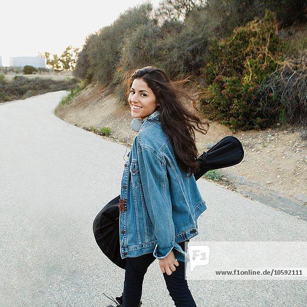 Junge Frau mit Gitarre  die über die Schulter schaut und lächelt  Woodland Hills  Kalifornien  USA