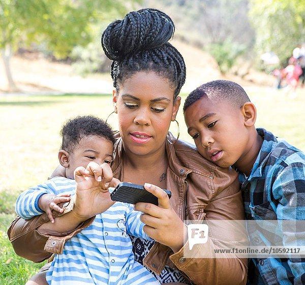 Mutter und Kinder sitzen auf dem Smartphone und schauen nach unten.