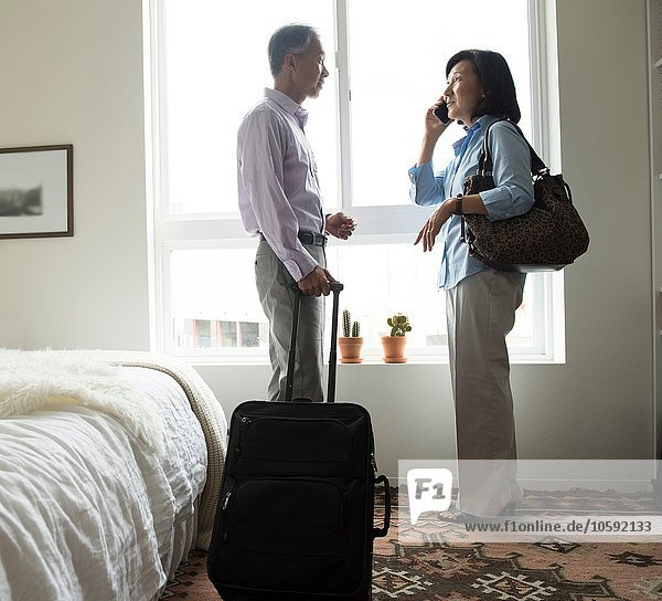 Mature couple standing in hotel room with suitcase using cellular phone
