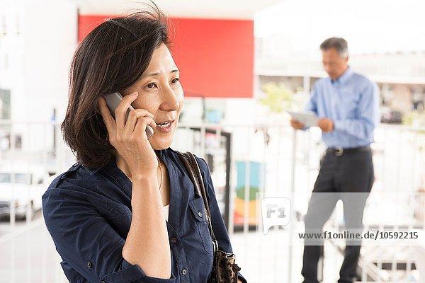 Kopf und Schultern einer reifen Frau  die auf dem Smartphone spricht und wegschaut.