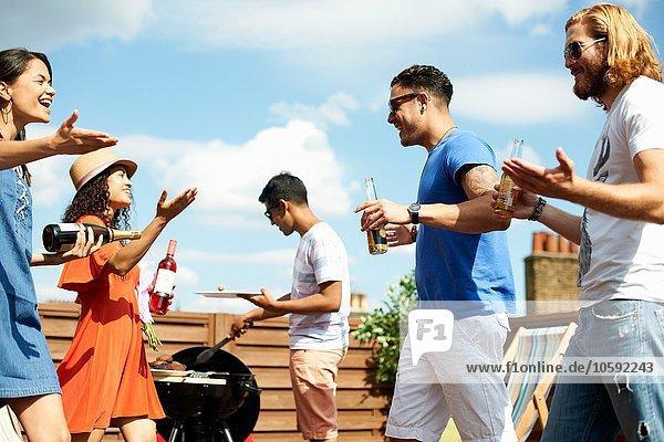 Weibliche und männliche Freunde grüßen am Dachgrill