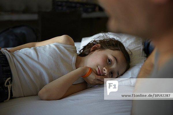 Mädchen auf dem Bett liegend  Vater beobachtend
