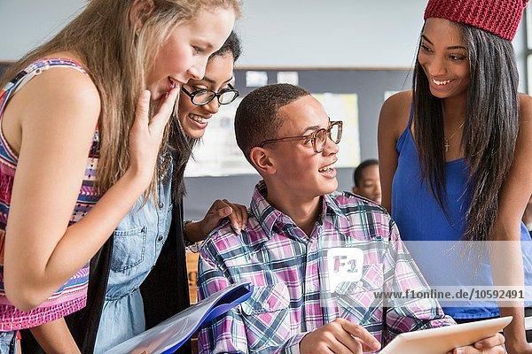 Gruppe von Schülern im Klassenzimmer  die sich ein digitales Tablett anschauen