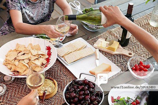 Abgeschnittene Ansicht der weiblichen Freunde beim Weinschenken am Mittagstisch