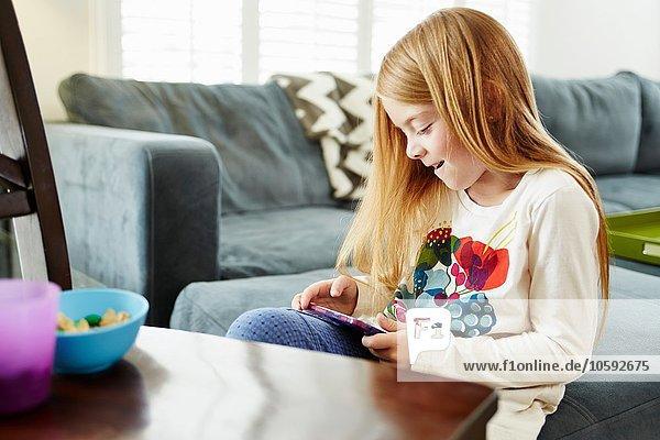 Mädchen mit digitalem Tablett auf Sofa im Wohnzimmer
