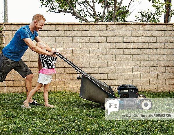 Vater und Tochter mähen Rasen im Hinterhof