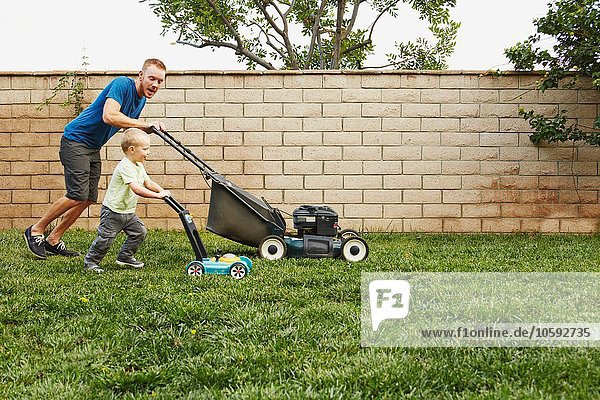 Vater und Sohn mähen Rasen im Hinterhof
