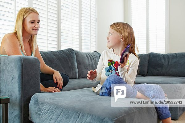 Mother and daughter using digital tablet on sofa in living room