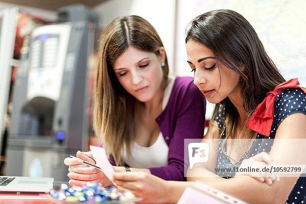 Zwei junge Frauen sitzen zusammen und studieren