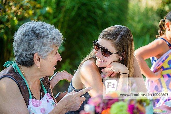 Mittlere erwachsene Frau im Gespräch mit älterer Frau im Garten