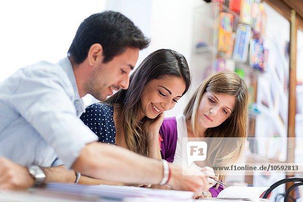 Drei Freunde sitzen zusammen und studieren