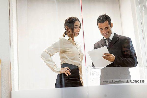Geschäftsmann und Geschäftsfrau beim Betrachten von Dokumenten  bei Gesprächen