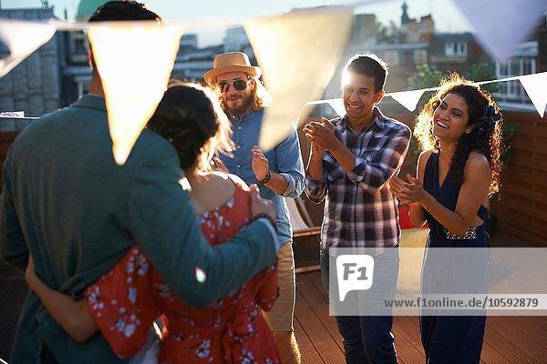 Freunde gratulieren dem Paar bei der Verlobungsparty am frühen Abend