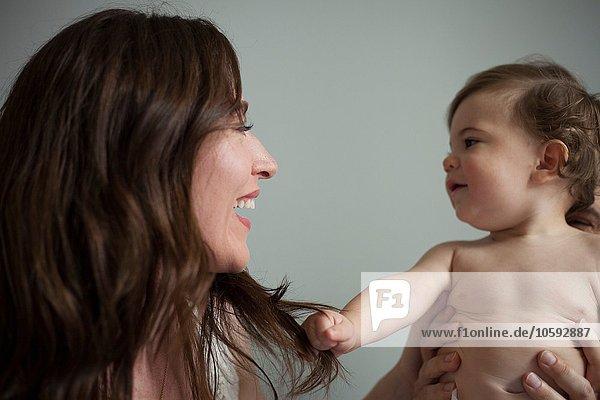 Mutter mit nacktem Brustkorb  von Angesicht zu Angesicht lächelnd