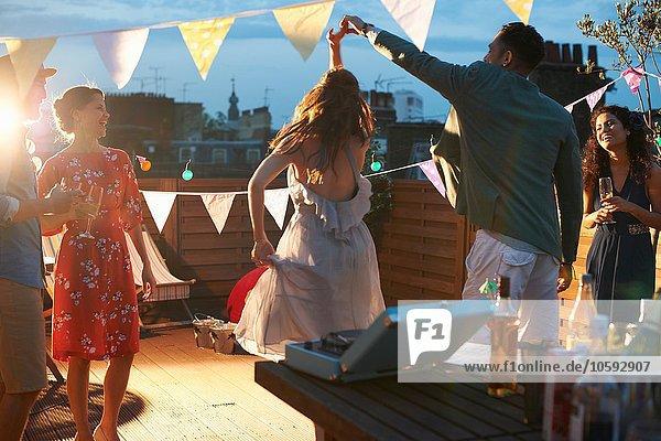 Freunde tanzen auf der Party am frühen Abend