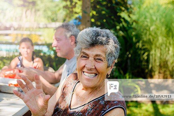 Seniorenfrau im Freien mit Familie  die auf die Kamera schaut und lächelt.