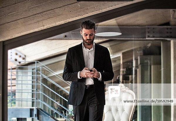 Mittlerer Erwachsener Mann im Anzug  der das Smartphone hält und nach unten schaut.