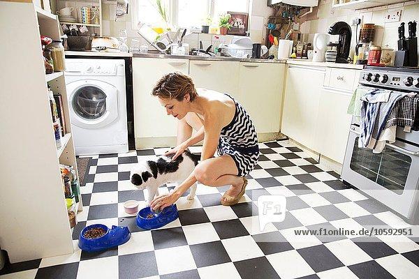 Mid adult woman feeding cat in kitchen