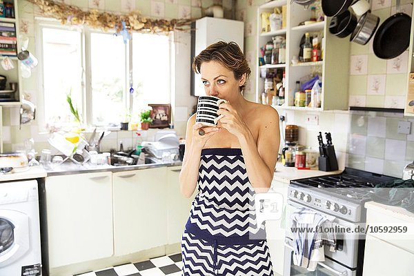 Mid adult woman drinking coffee in kitchen