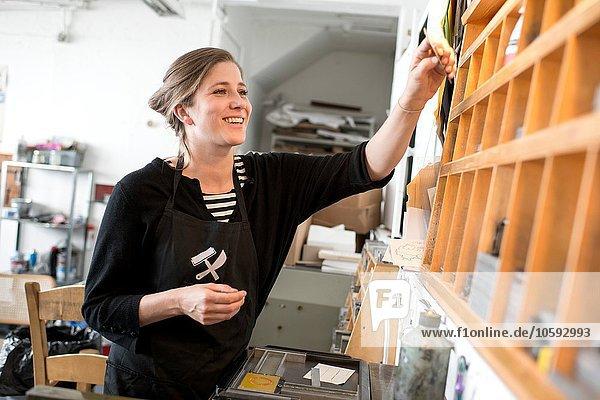Druckerin wählt Buchdruckbuchstaben aus dem Werkstatt-Regal aus