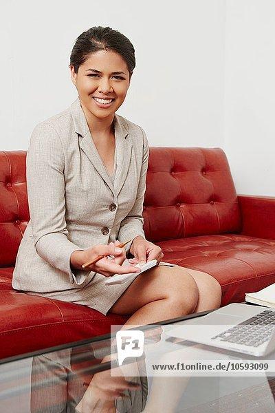 Porträt einer mittleren erwachsenen Geschäftsfrau auf dem Sofa sitzend  mit Laptop