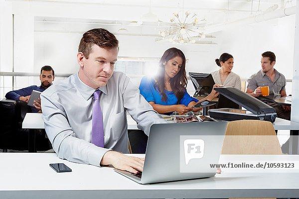 Mittlerer erwachsener Geschäftsmann am Schreibtisch sitzend  mit Laptop  im Hintergrund arbeitende Kollegen