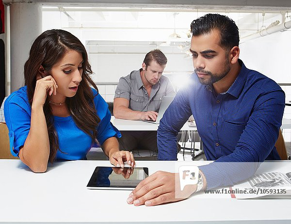 Geschäftsfrau und Geschäftsmann am Schreibtisch sitzend  mit Blick auf das digitale Tablett