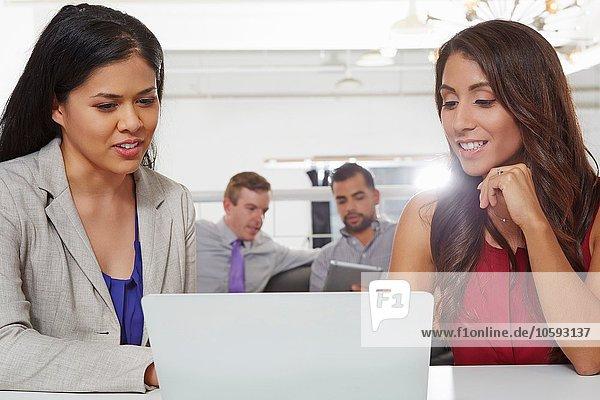 Zwei Geschäftsfrauen sitzen am Schreibtisch und schauen auf den Laptop.