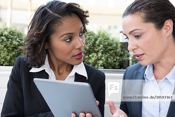 Zwei Geschäftsfrauen beim Betrachten des digitalen Tabletts im Freien