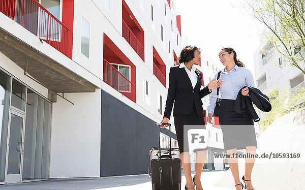 Zwei Geschäftsfrauen gehen die Straße entlang und ziehen den Koffer.