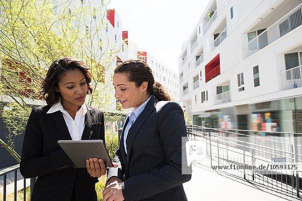 Zwei Geschäftsfrauen beim Betrachten des digitalen Tabletts  ouytdoors