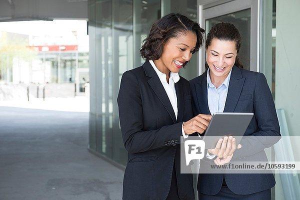 Zwei Geschäftsfrauen  die sich das digitale Tablett ansehen  im Freien