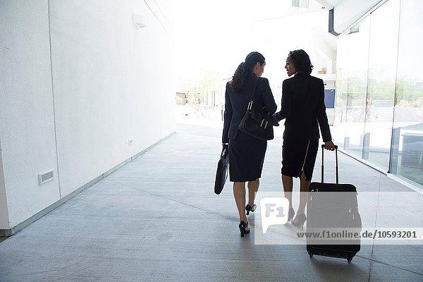 Zwei Geschäftsfrauen im Gang  Koffer ziehen  Rückansicht