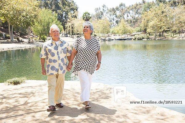 Seniorenpaar geht Hand in Hand am See entlang