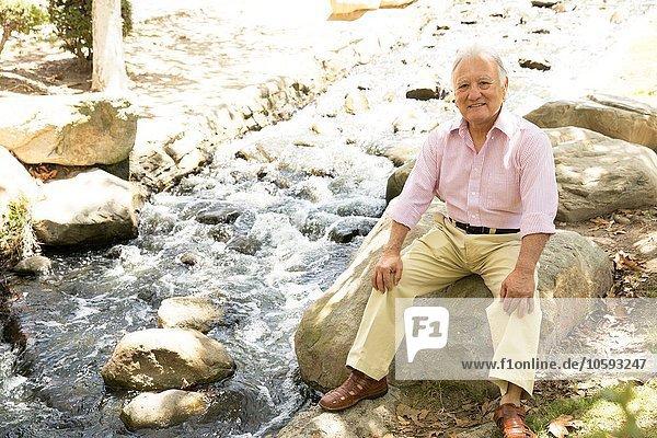 Porträt eines älteren Mannes  der auf einem Felsen sitzt  im Freien