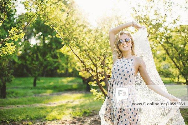 Junge Frau im Obstgarten in ärmellosem Kleid und Sonnenbrille mit Spitzenstoff  mit lächelndem Blick auf die Kamera.