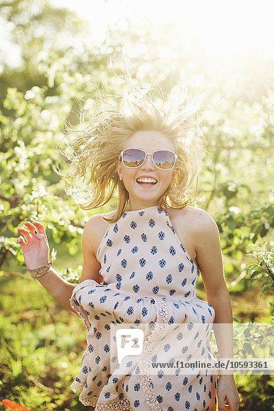 Junge Frau in ärmellosem Kleid und Sonnenbrille springender Blick auf die Kamera lächelnd