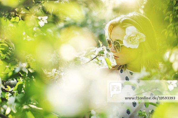 Blick durch das Laub der jungen Frau  Blüte im Haar  mit Nasenbolzen und Sonnenbrille zum wegschauen