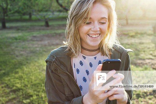 Kopf und Schultern einer jungen Frau mit Smartphone  die lächelnd nach unten schaut.