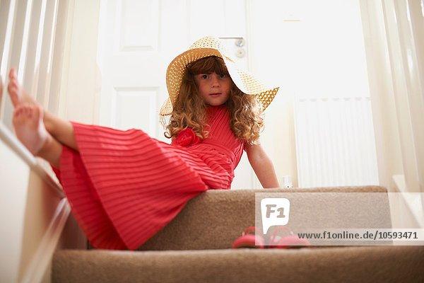 Portrait des Mädchens auf der Treppe mit Strohhut Portrait des Mädchens auf der Treppe mit Strohhut