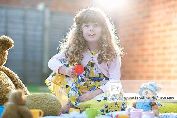 Mädchen mit Teddybär Picknick im Garten hält Spielzeug Teetasse