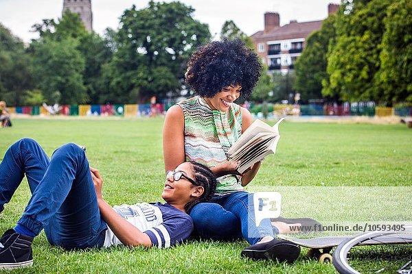 Junge und Mutter entspannen und lesen Buch im Park