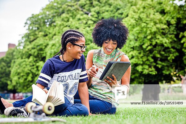 Boy and mother reading digital tablet in park