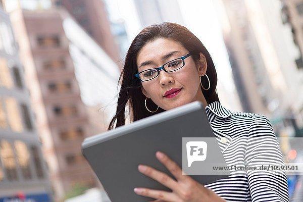 Geschäftsfrau mit digitalem Tablett auf der Straße
