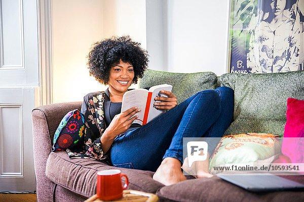 Reife Frau entspannt auf dem Wohnzimmersofa Lesebuch