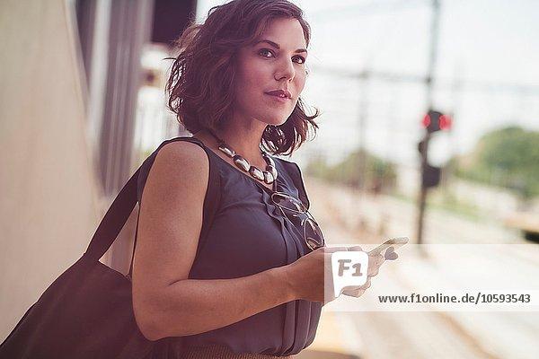 Mittlere erwachsene Frau  die am Bahnhof wartet und ein Smartphone hält.