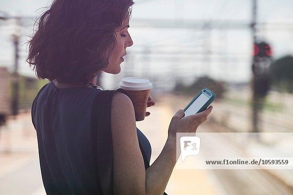 Mittlere erwachsene Frau  die am Bahnhof wartet  mit dem Smartphone  Kaffeetasse haltend