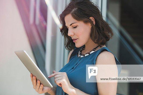 Mittlere erwachsene Frau im Freien  mit digitalem Tablett