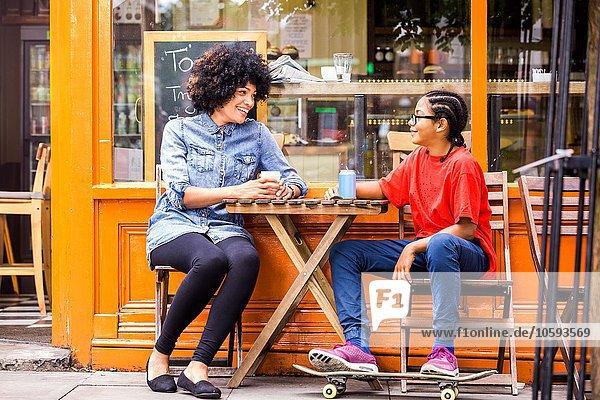 Skateboarding Junge und Mutter sitzen auf dem Bürgersteig Cafe